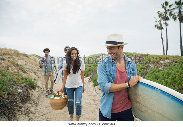 Friends carrying surfboard and picnic basket beach path - Stock Image