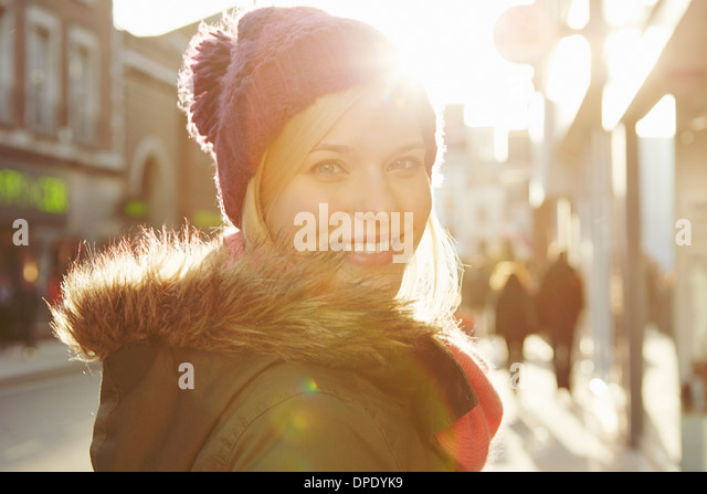 Portrait of young woman wearing knit hat, looking over shoulder - Stock Image
