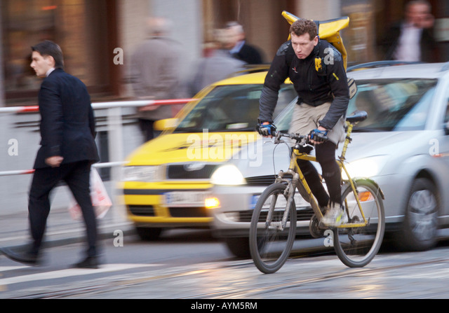 Bicycle courier fighting his way through the busy city streets of Prague, Czech Republic during the late afternoon. - Stock Image