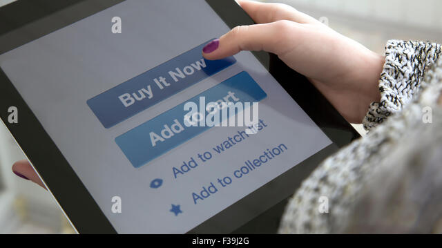 Internet shopping Female fingers clicking on BUY button - Stock Image