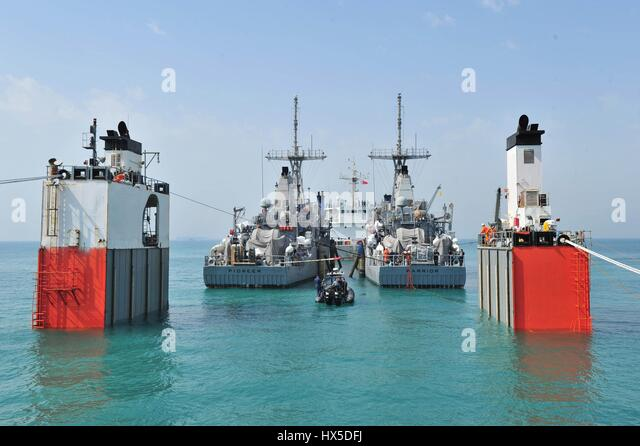 In calm turquoise waters two mine countermeasure ships USS Pioneer and USS Warrior prepare for transport behind - Stock Image
