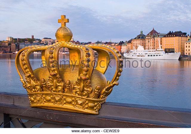 Ornamental crown on Skeppsholmen Bridge, with Gamla Stan (The old town) beyond. Stockholm, Sweden, - Stock Image
