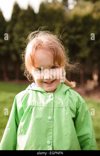 Portrait of a young girl at a park with a rain coat on. This lifestyle photo was shot with natural light. - Stock-Bilder