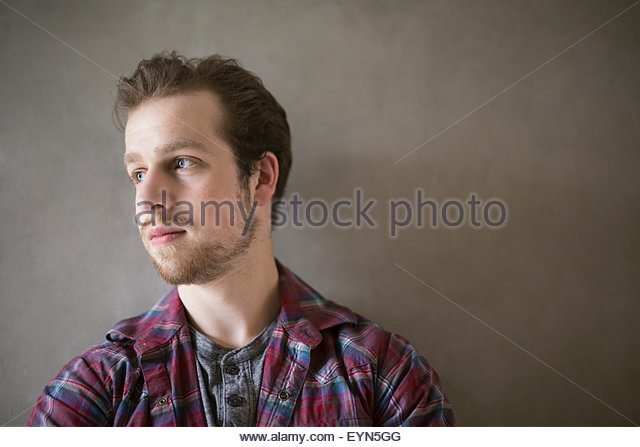 Pensive man with beard looking away against gray background - Stock-Bilder