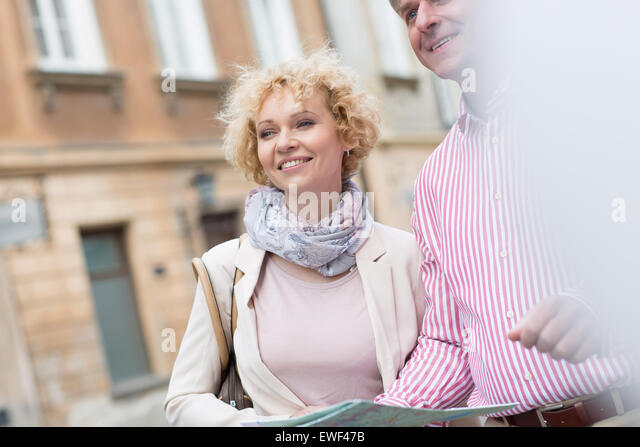 Happy middle-aged couple with map in city - Stock Image