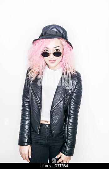 A young woman with pink hair posing in a studio looking cool. - Stock Image