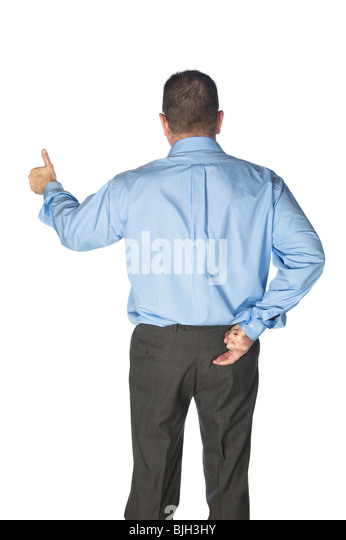 A businessman gives a thumbs up and has his fingers crossed behind his back as if lying or deceiving his clients. - Stock Image