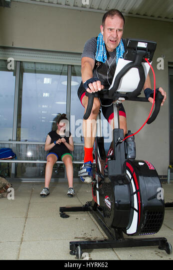Middle aged man trying hard on a stationary cycle trainer - Stock Image