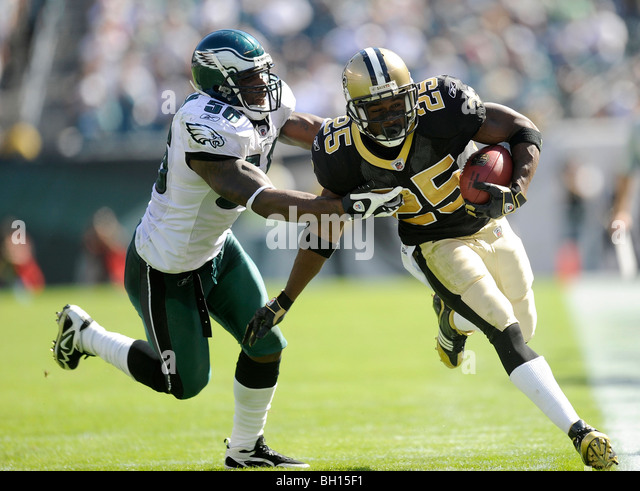 Reggie Bush #25 of the New Orleans Saints runs with the ball as Akeem Jordan #56 of the Philadelphia Eagles defends - Stock Image