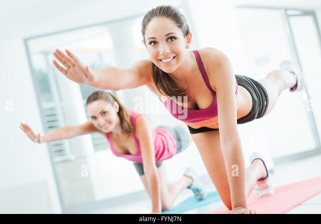 Sporty young women at the gym doing pilates workout on a mat, fitness and healthy lifestyle concept - Stock Image