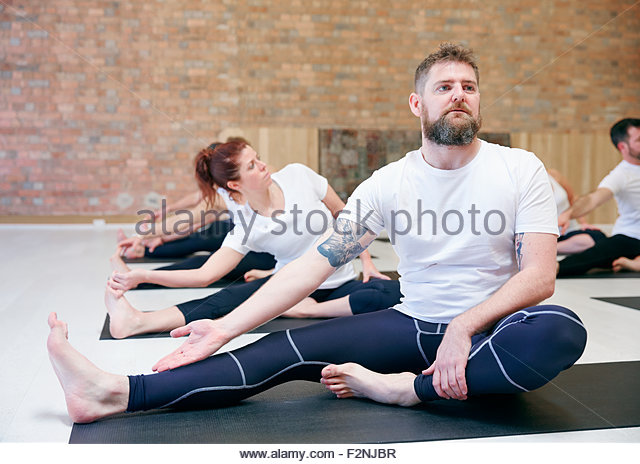 Students practicing yoga in class - Stock Image