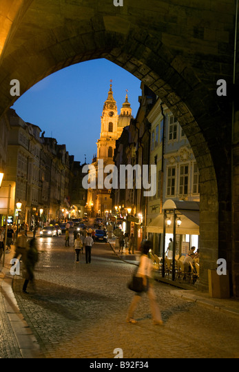 People wandering the cobbled streets of Mala Strana at night Prague Czech Republic - Stock Image