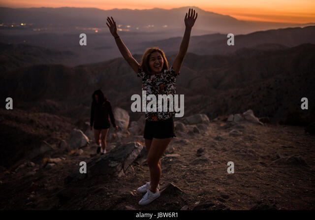 Portrait of young woman with hands raised in Joshua Tree National Park at sunset, California, USA - Stock-Bilder