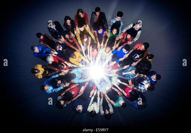 Diverse crowd around bright light - Stock Image