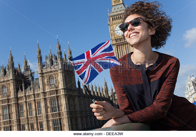 Portrait of smiling woman with British flag in front of Big Ben clocktower - Stock Image