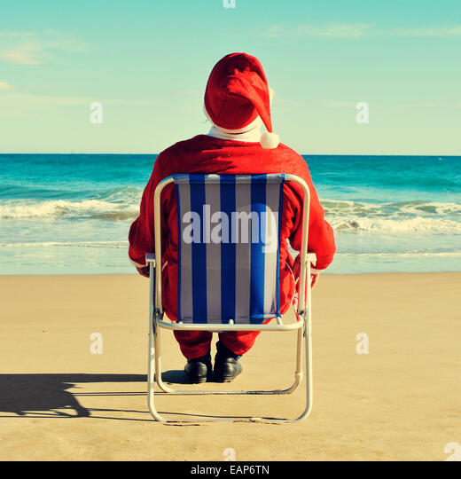 santa claus sitting in a beach chair on the beach - Stock Image