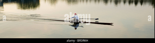 A lone rowing scull cuts through the river's glassy surface as the rower gets some early morning exercise. - Stock Image
