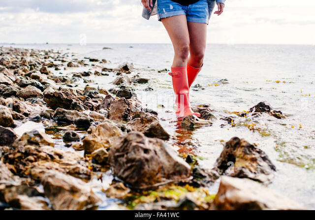 Low section of woman walking on beach - Stock Image