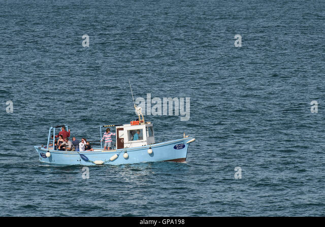 Island Maid, a pleasure boat full of holidaymakers mackerel fishing in Newquay Bay, Cornwall. - Stock Image
