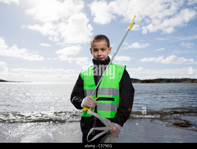 Boy in safety vest cleaning beach - Stock Image