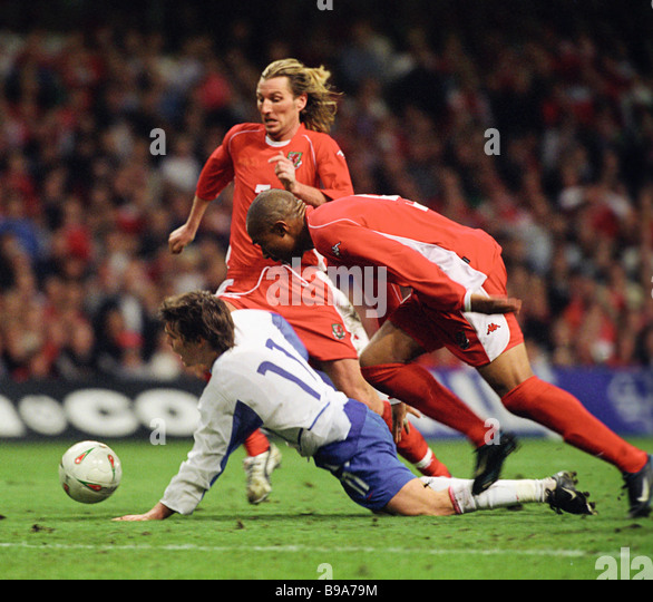 Tense moment during match between Russian wearing white uniforms and Welsh select teams Welsh attacker John Hartson - Stock Image