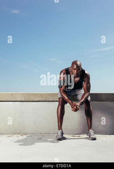 Portrait of fit young man relaxing after his running training. African male model taking rest after running workout. - Stock Image
