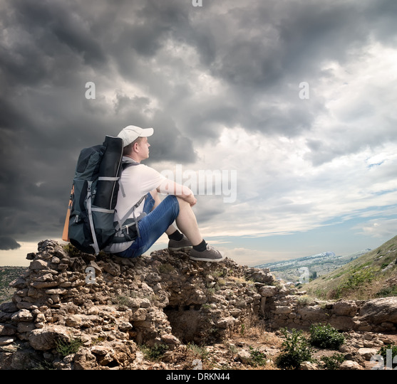 Tourist sitting on the rocks under cloudy sky - Stock Image