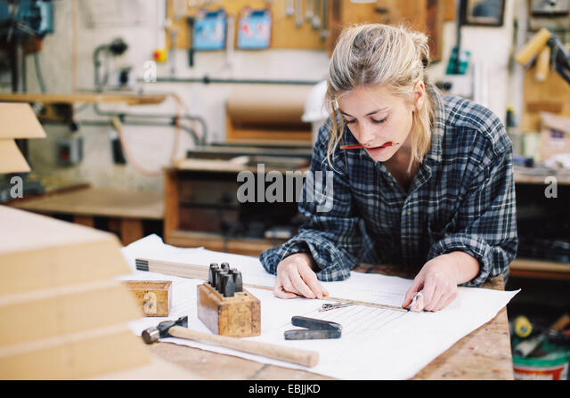 Young craftswoman measuring blueprint on workbench in pipe organ workshop - Stock Image