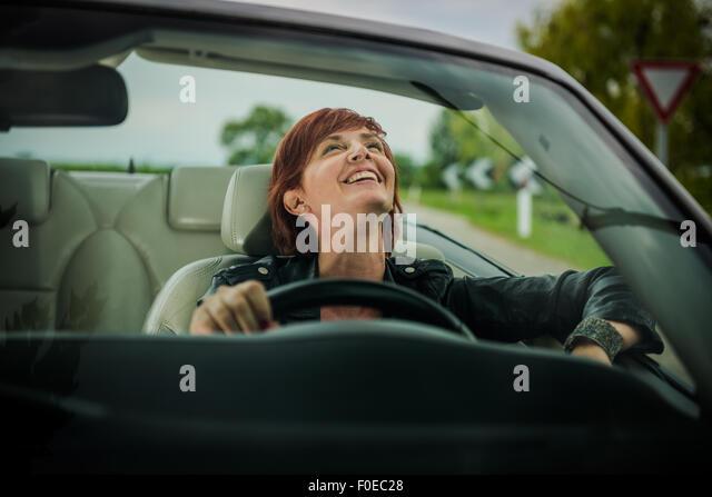 Woman enjoying driving her convertible car - Stock Image