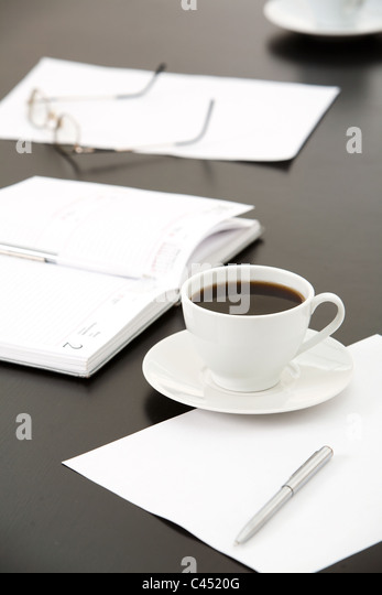 Close-up of cup of coffee, papers, notebook, pens, eyeglasses on the table - Stock-Bilder