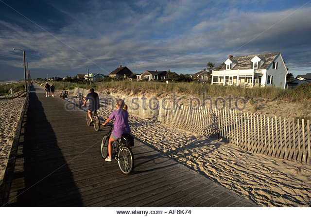 Delaware Rehoboth Beach boardwalk bikers bicycles beach rental cottages - Stock Image