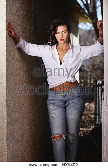 Portraits of a brunette woman with white top and blue jeans - Stock Image