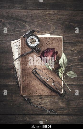 Still life with red rose on an old book placed with antique pocket watch on rustic wooden table - Stock Image