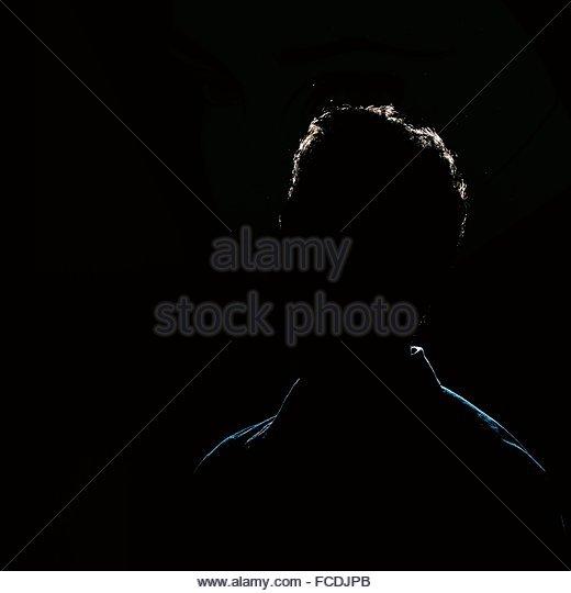 Silhouette Man Against Black Background - Stock-Bilder
