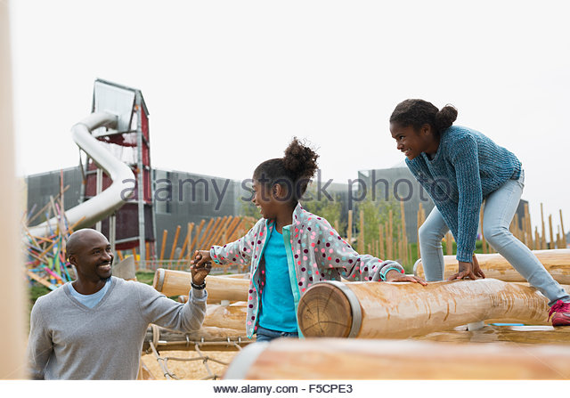 Father helping daughter climb logs at playground - Stock Image