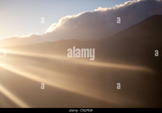 Clouds and mountains in sunlight - Stock Image
