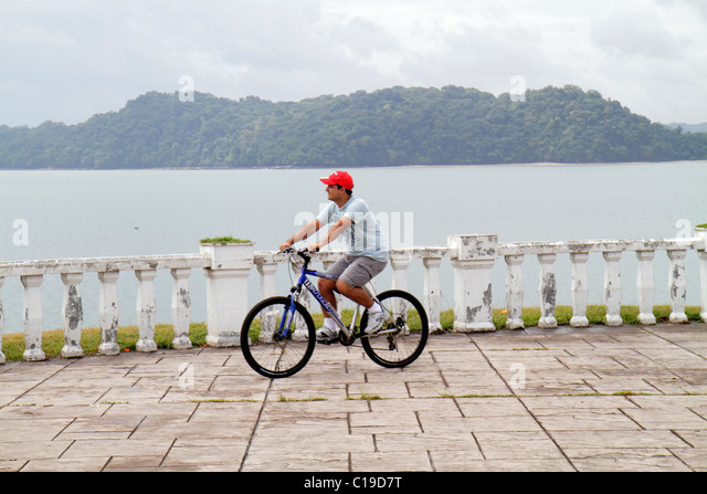 Panama City Panama Amador Panama Canal promenade balustrade Hispanic man bicycle bike cycling leisure exercise riding - Stock Image