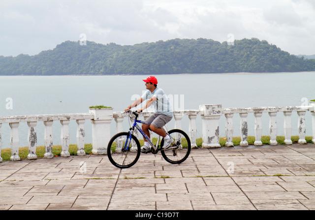 Panama Panama City Amador Panama Canal promenade balustrade Hispanic man bicycle bike cycling leisure exercise riding - Stock Image