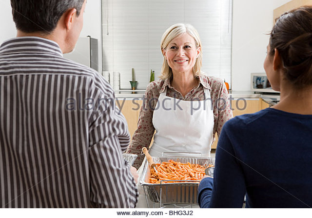 Woman volunteering at soup kitchen - Stock Image