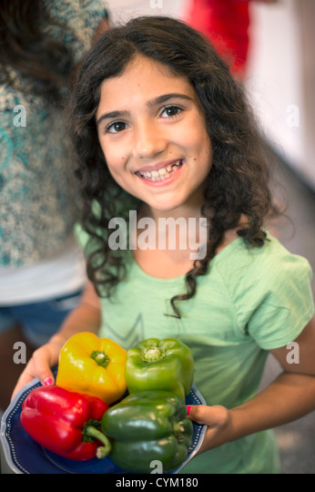 Smiling girl holding bowl of peppers - Stock Image