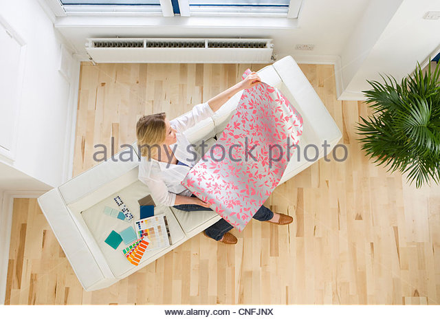 Woman on sofa looking at wallpaper sample - Stock Image