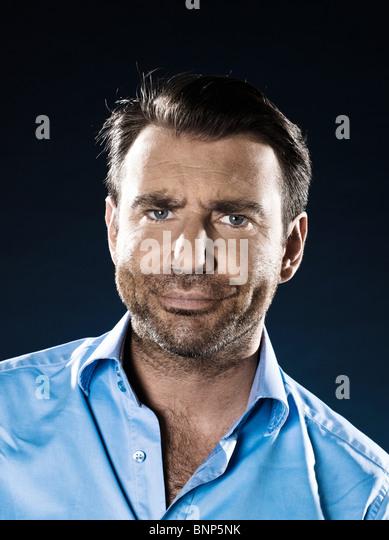 caucasian man unshaven suspicious doubt portrait isolated studio on black background - Stock Image