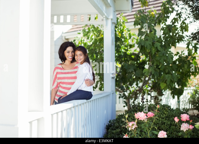 Portrait of smiling mother and daughter on porch - Stock Image