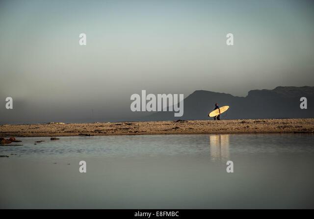 Surfers walking on beach - Stock-Bilder
