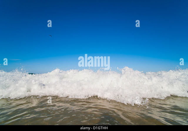Bright blue sky and waves breaking at Surfers Paradise Beach, Gold Coast, Queensland, Australia, Pacific - Stock Image