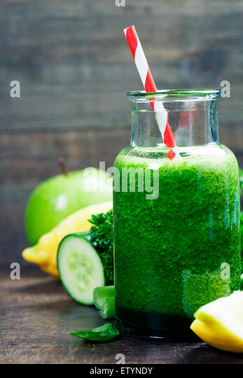 Fresh organic green smoothie with spinach, cucumber, parsley, celery and lemon on wooden background - Stock Image