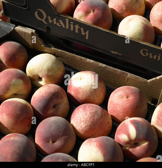 Peaches on market stall - Stock Image