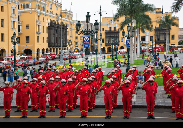 Peru. Members of Lima's fire brigade parade outside Lima Cathedral on a corner of Plaza Mayor. - Stock Image