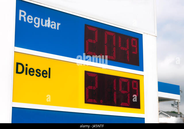 Sign advertising very low prices at a gasoline station. - Stock Image