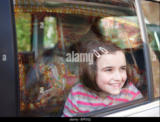 girl smiling and looking out of car window at fairground ride with reflection of carousel in glass - Stock Image